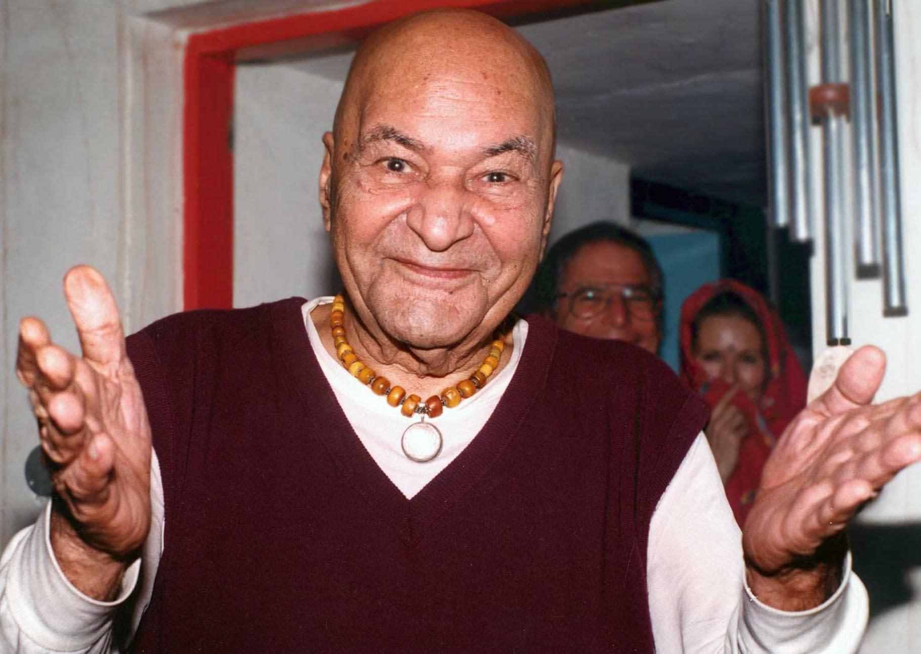 Papaji lächelt mit ausgebreiteten Armen in die Kammera