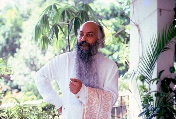 Acharya Rajneesh in white clothes outside