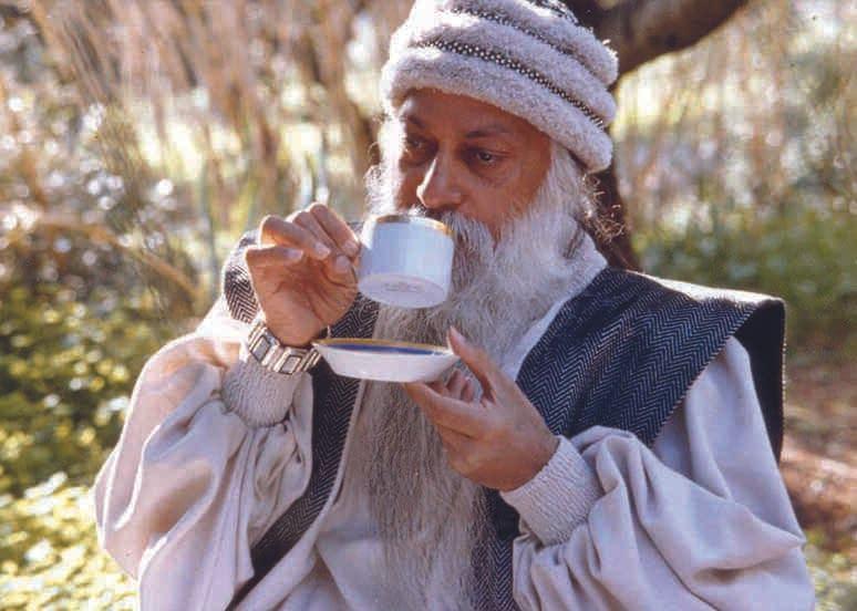 Osho like a blue white Santa dronking tea